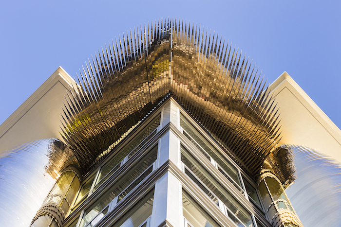Golden spikes fan out from the upper floor of a building, reflecting the street below while similar spikes fan out vertically from the corners of the building, reflecting the sky.
